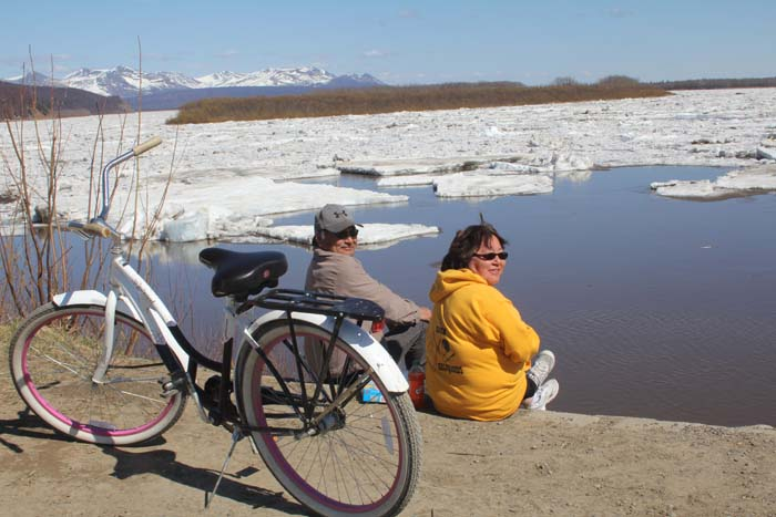 Bev and Nick Nicolai watching the ice flow by enjoying a dinner of Vienna sausages.  Note the classy pink rims on the bike.