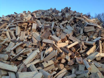 One of several small mountains of split firewood prior to being shipped downstream